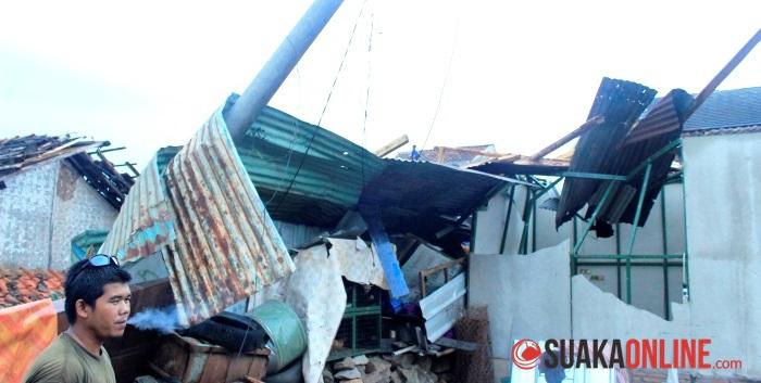Sebuah tiang listrik roboh dan menimpa rumah akibat angin kencang. (Foto: Dede Lukman)
