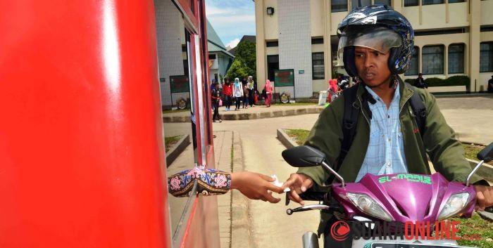 Seorang pengendara sepeda motor saat memberikan karcis parkir kepada petugas parkir di UIN SGD Bandung. (Foto: WIsma Putra)