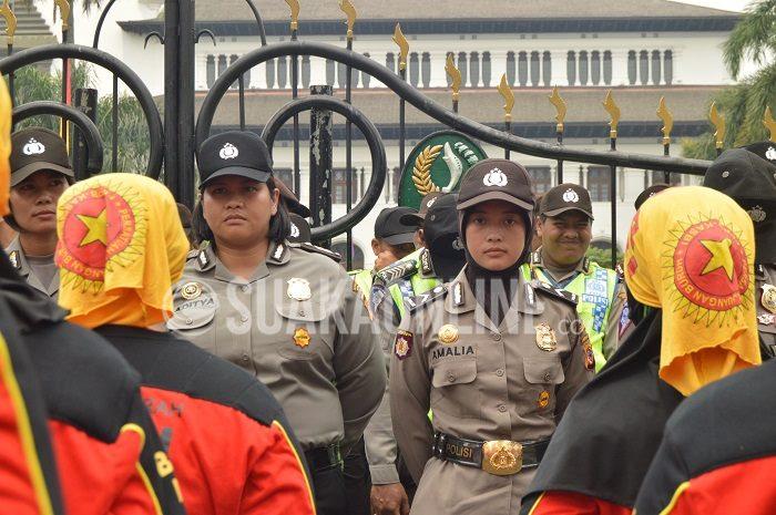 Peringatan hari buruh internasional yang jatuh pada Jumat (1/5/2015), diwarnai aksi unjuk rasa dari Kongres Aliansi Serikat Buruh Indonesia (KASBI). Demi keamanan situasi, polisi berjaga di halaman Gedung Sate, berhadapan dengan ratusan masa. (Isthiqonita/Suaka)