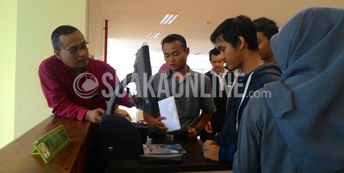 Pengunjung perpustakaan UIN Bandung tengah mempelajari proses peminjaman buku secara mandiri.