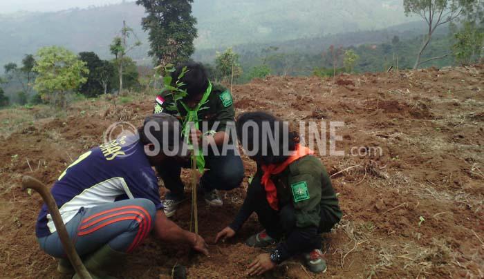 Dua orang anggota Mahapeka dan masyarakat sedang melakukan penanaman pohon di Desa Ciporeat, Kecamatan Cilengkrang, Kabupaten Bandung dalam aksi penanaman pohon yang dilakukan oleh UKM Mahapeka UIN SGD Bandung, Sabtu (26/12/2015). (Suaka/Adi Permana).