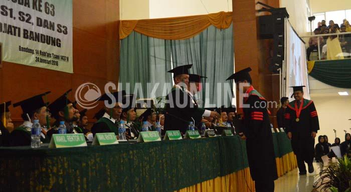 Rektor UIN SGD Bandung, Mahmud memberikan izajah kepada salah seorang wisudawan dalam wisuda ke-63 UIN SGD Bandung di Aula Multipurpose, Minggu (24/1/2015).