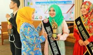 Kepala Bidan Badan Kependudukan dan Keluarga Berencana Nasional (BKKBN) Provinsi Jawa Barat, (kiri) tengah memberikan piala penghargaan kepada Duta Mahasiswa GenRe Jawa Barat (kanan), Mutiara Jais, Jum'at (15/5/2015). (Dok. Pribadi)