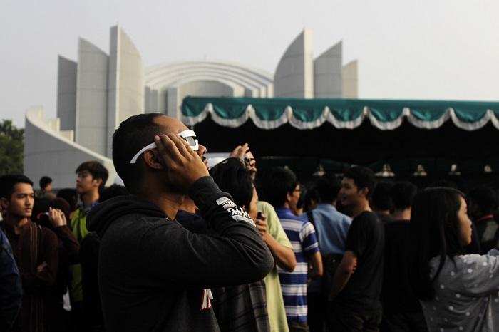 Kacamata Gerhana Matahari – Seorang pengunjung menikmati proses gerhana matahari menggunakan kacamata khusus di lokasi pengamatan gerhana matahari di Monumen Perjuangan, Dipati Ukur, Kota Bandung, Rabu (09/03/2016). Kacamata khusus Gerhana matahari didesain seperti kacamata 3D namun dengan bahan kaca yang berbeda. Kacamata gerhana matahari menggunakan filter Neutral Density 5 (ND5) untuk mengurangi intensitas matahari 100.000 kali. (Mohammad Aziz Pratomo/ Magang)