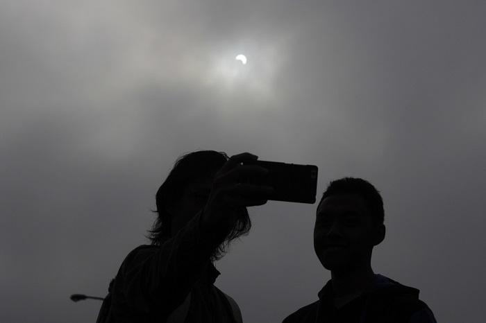Nampak dua orang mahasiswa berfoto selfie saat gerhana matahari mencapai punyanya pada 88 persen, Rabu (9/3/2016) di Monumen Perjuangan, Dipati Ukur, Bandung.
