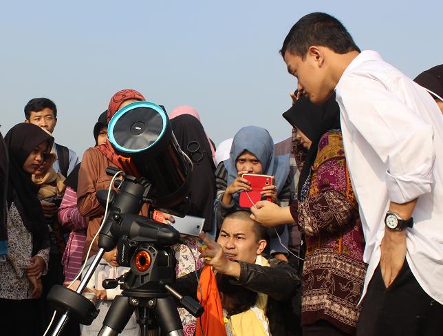 Seorang bapak dan anaknya menggunakan teleskop saat melihat gerhana matahari di lapangan terbuka Lab Terpadu UIN SGD Bandung, Rabu (9/3). Di Bandung hanya 88 persen terlihat matahari yang tertutup bulan, namun antusiasme mahasiswa UIN SGD Bandung untuk melihat fenomena alam tersebut membuat gedung Lab Terpadu padat pengunjung.(Puji Fauziah/ Magang)