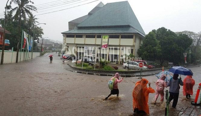 UIN Bandung Banjir -- Beberapa masyarakat melintasi jlan utama Kampus UIN SGD Bandung yang digenangi air akibat hujan deras, Sabtu (9/4/2016) tadi. Ini membuktikan drainase Kampus yang belum berfungsi maksimal. (Doni Anggola/ Magang)
