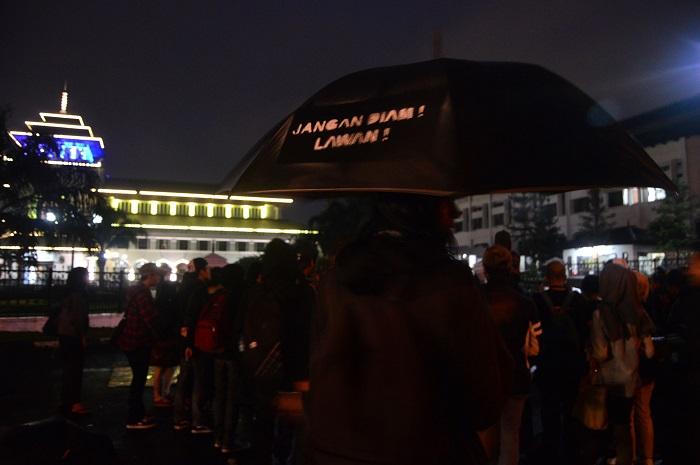 Salah satu peserta menggunakan payung hitam pada Aksi Kamisan Bandung, Jum'at (23/6/2016) di depan gerbang Gedung Sate, Bandung. Payung hitam berisi tulisan Jangan Diam! Lawan! Menjadi tanda Aksi Kamisan Bandung merindukan tegaknya keadilan di Indonesia. (SUAKA/ Mohammad Aziz Pratomo)