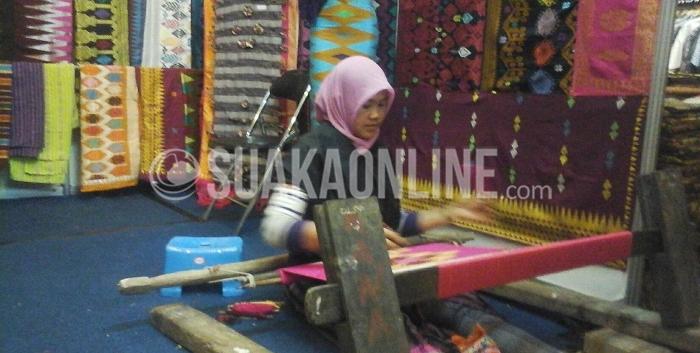 Seorang pengrajin kain tengah berada di pameran Gelar Kain Nusantara di Graha Manggala Siliwangi, Jalan Aceh Kota Bandung, Rabu (3/8/2016). Dalam pameran ini terdapat sekitar 90 tenant, pengrajin dan pengusaha kain seluruh Indonesia. (SUAKA / Nuru Fitry)