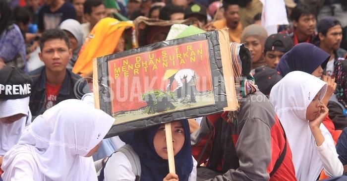 Massa yang tergabung dalam aksi Hajat Tani menuntut Komitmen Land Reform Presiden Joko Widodo dalam rangka Hari Tani ke-56 di depan Gedung Sate, Bandung, Rabu (21/9/2016). Land Reform adalah pengembalian hak tanah kepada rakyat untuk kemakmuran dan kesejahteraan yang merupakan program kerja Presiden Indonesia, Joko Widodo. (SUAKA / Elya Rhafsanzani)