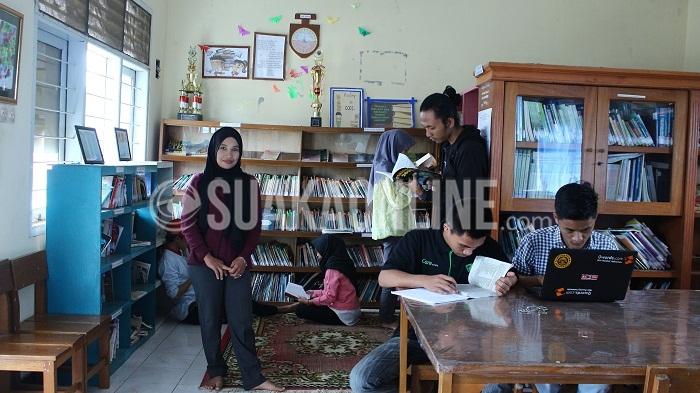 Lia Yulianti (kerudung hitam) saat berada di perpustakaan Taman Pamekar, Sukabumi, Minggu, (11/09/2016). Kecintaannya terhadap membaca membuat ia mumutuskan untuk mengelola perpustakaan sejak pertengahan November 2002 lalu. (SUAKA/Purna Irawan)