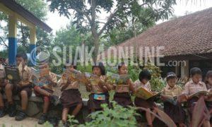 """Para siswa SDN Mulyasejati IV Desa Mulyasejati Kecamatan Ciampel Karawang sedang asyik membaca buku di halaman kelasnya dalam kegiatan """"Aku Kembali ke-sekolah"""" yang dilaksanakan oleh Semesta Literasi, Rabu (03/12/16). Sesi membaca tersebut dinamakan Piknik buku, dimana para siswa bebas membaca buku apapun yang disediakan, dari buku ilmu astronomi hinga komik. (Nizar Al Fadillah)"""
