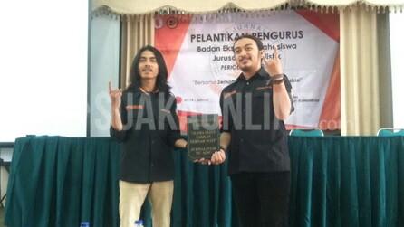 Presiden Mahasiswa (Presma) Domisioner, Adi Maulana Ibrahim (kiri) menyerahkan plakat sebagai simbolis dalam prosesi serah terima jabatan kepada Presma terpilih, Thoudy Badai Rif'anbillah (kanan) dalam acara Pelantikan Badan Eksekutif Mahasiswa Jurusan (BEM-J) Jurnalistik periode 2016-2017, Kamis (9/2/2017). (Edi Setio /Magang)